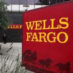 "Wells Fargo shares edge up on Tuesday, bank faced with restrictions as it fails ""living will"" test"