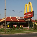 McDonald's Corp share price down, lifts pay at company-owned US restaurants